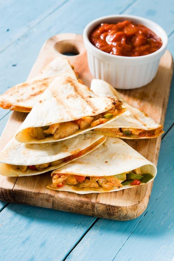 Quesadilla mexicano con el pollo, el queso y pimientas en la madera azul imagenes de archivo
