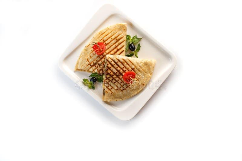 Quesadilla mit Gemüse in einer weißen Platte auf einem lokalisierten weißen Hintergrund stockbilder