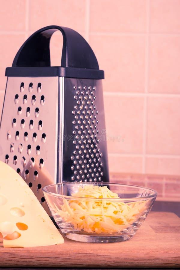 Queso amarillo rallado con el rallador en la cocina imágenes de archivo libres de regalías