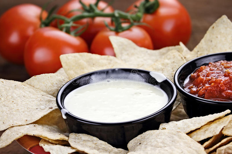 Queso Blanco White Cheese Sauce. Queso Blanco or White Cheese Sauce with corn tortilla chips, salsa and fresh tomatoes. Shallow depth of field with selective royalty free stock images