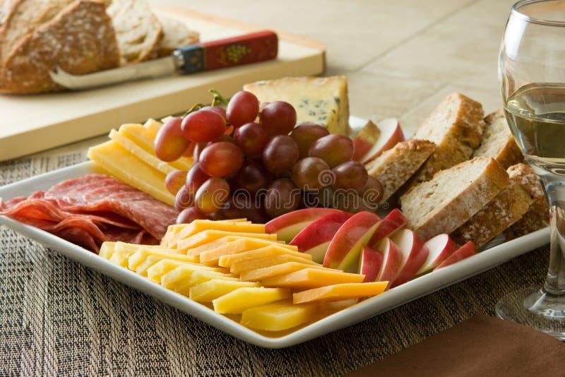 Queso, carne, pan, manzanas y uvas fotos de archivo