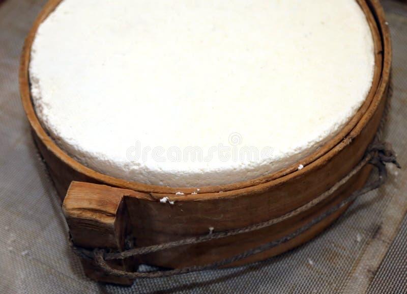 Queso con el molde de madera en la lechería de una choza de la montaña imagen de archivo libre de regalías