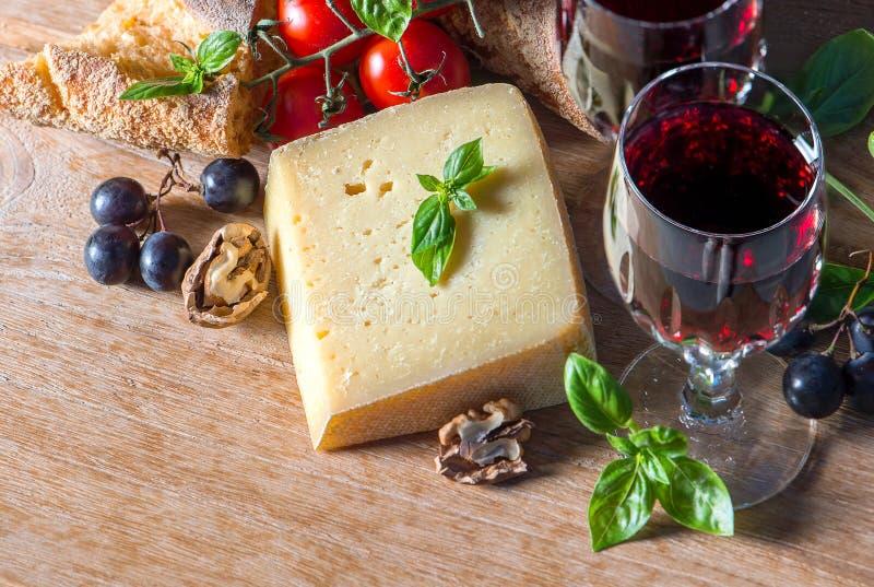 Queso con el vino rojo, las nueces, y las uvas Fondo del alimento fotografía de archivo libre de regalías