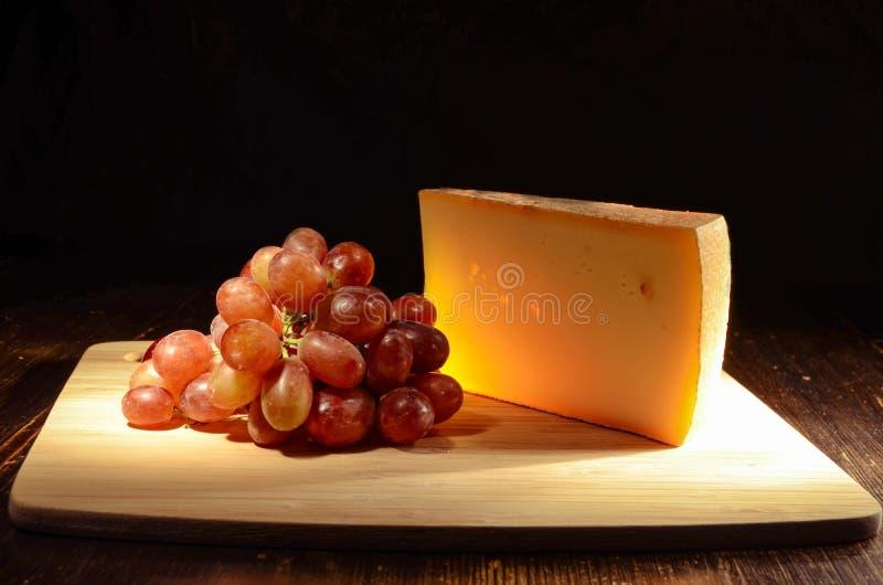 Queso con las uvas en un tablero de madera fotos de archivo
