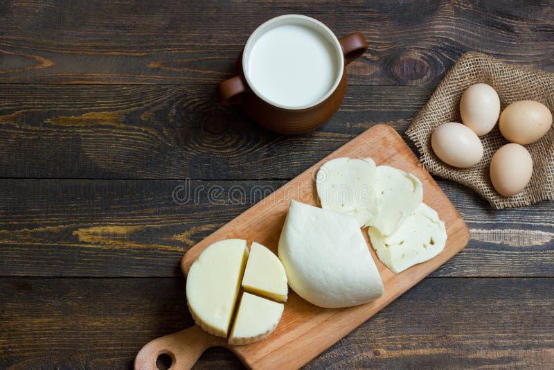 Queso con leche en una tabla de madera Visión superior imagenes de archivo