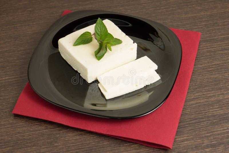 Queso cortado en plato negro con la servilleta foto de archivo