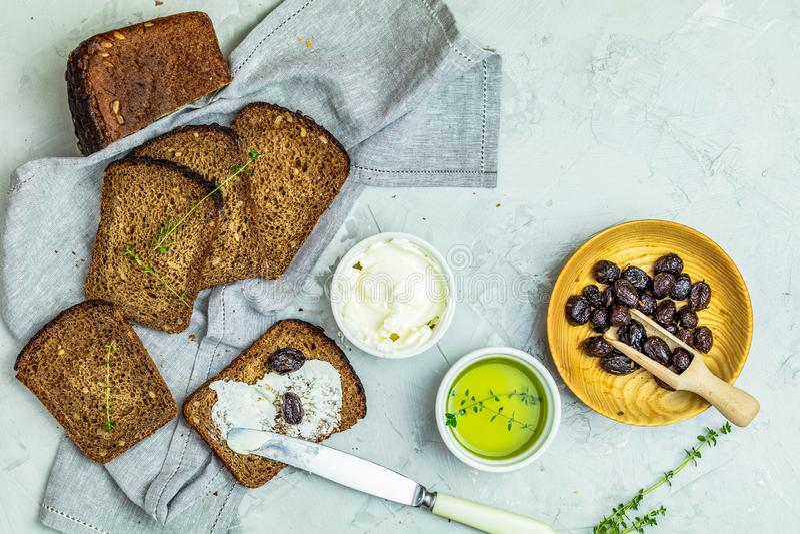 Queso cremoso del pan del trigo integral y aceitunas secadas imagen de archivo