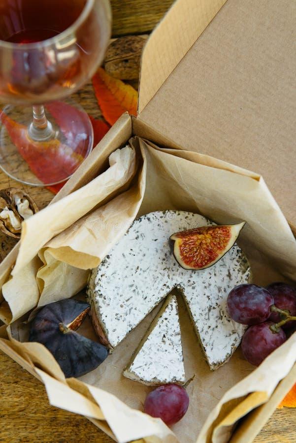 Queso de camembert en hierbas, higo, uva y vino tinto imagenes de archivo