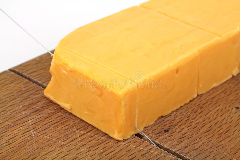Queso de Cheddar sostenido que es cortado fotografía de archivo libre de regalías