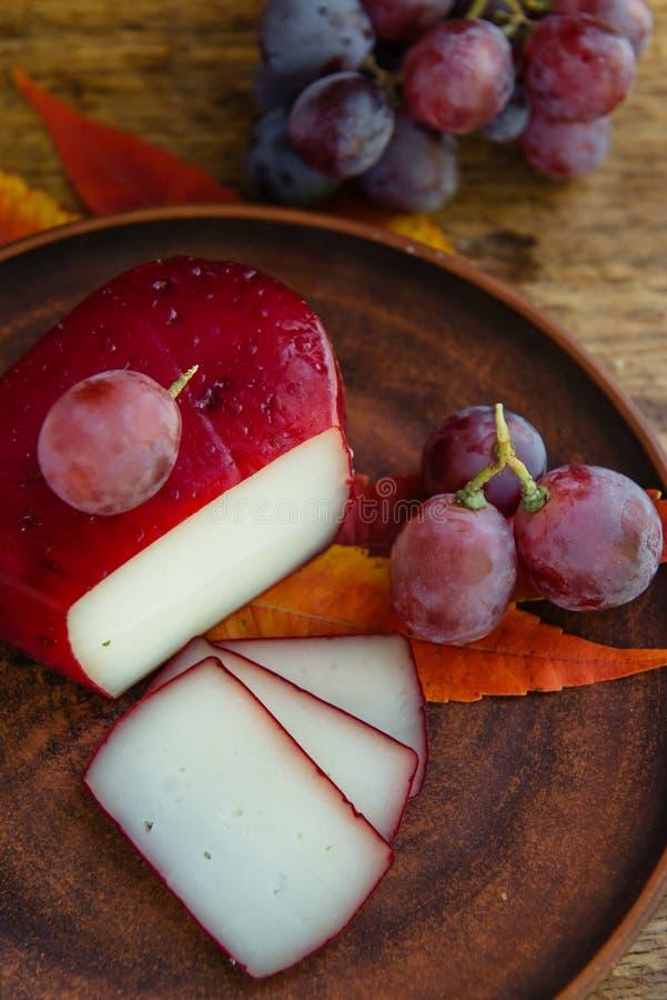 Queso de gouda hecho a mano en hierbas y frutas fotografía de archivo