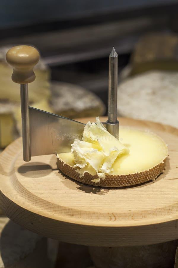 Queso de la leche cruda de Tete de moine con el girolle en tabla de cortar fotografía de archivo libre de regalías