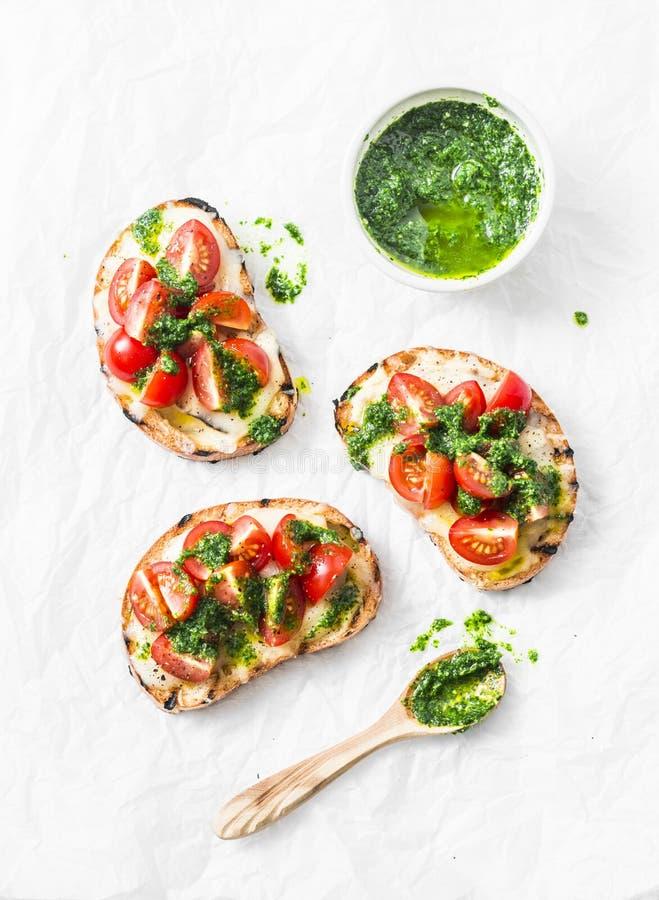 Queso de la mozzarella, tomates de cereza y bruschetta del pesto del arugula en el fondo ligero, visión superior Pesto y bocadill fotos de archivo