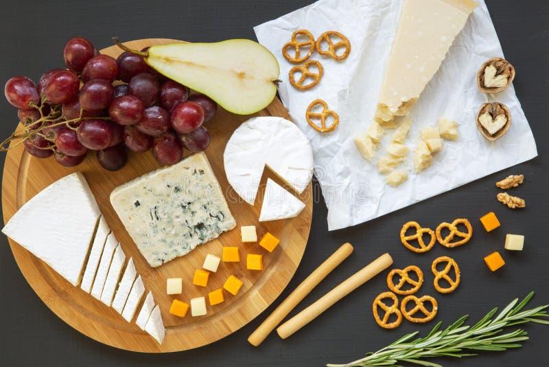 Queso de la prueba con los pretzeles, las frutas, las nueces y las barras de pan en fondo oscuro imagenes de archivo