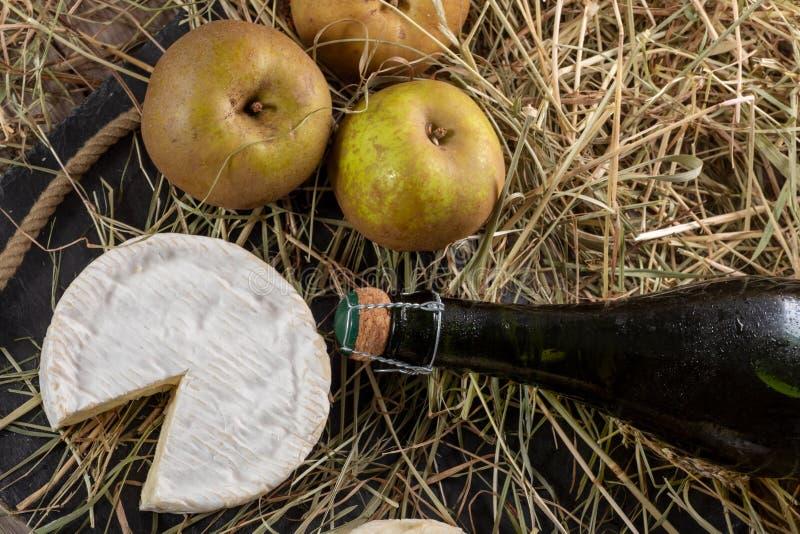 Queso del camembert, botella de sidra y manzanas foto de archivo