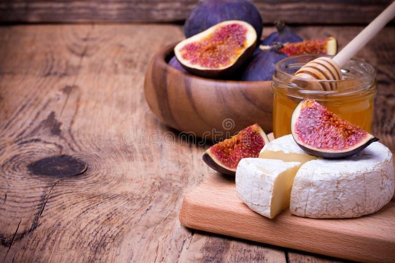 Queso del camembert con la miel y los higos en un tablero de madera foto de archivo libre de regalías