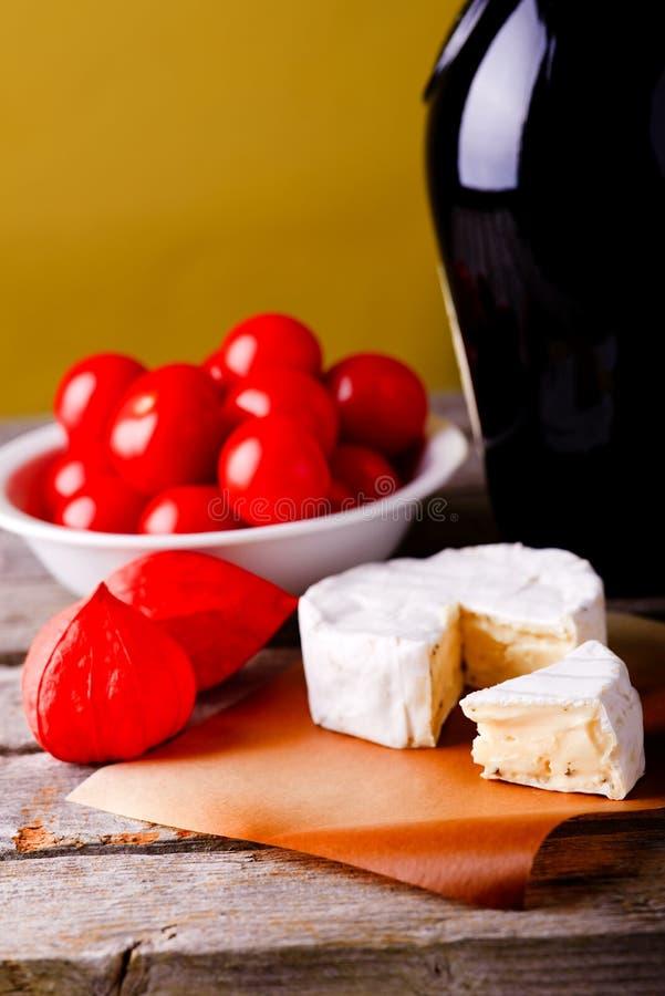 Queso del camembert delante del vino y de los tomates fotografía de archivo