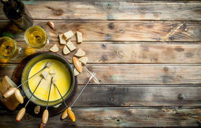 Queso delicioso de la 'fondue' con las rebanadas del pan y el vino blanco imagen de archivo