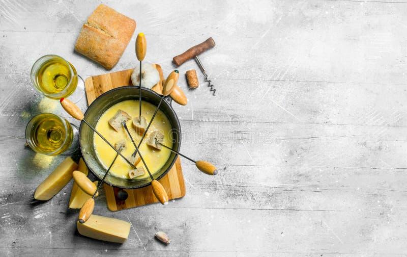 Queso delicioso de la 'fondue' con pan y el vino blanco fotografía de archivo