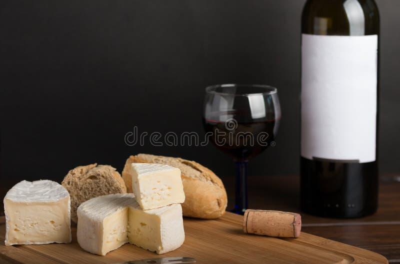 Queso en la tabla de madera con el vino rojo imagen de archivo