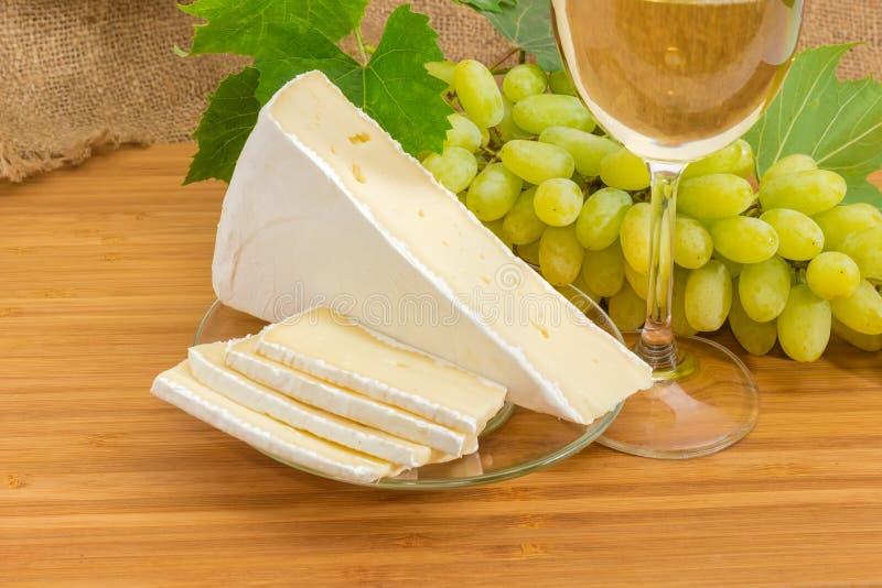 Queso en parte cortado del brie contra de las uvas blancas y el vino imagen de archivo libre de regalías