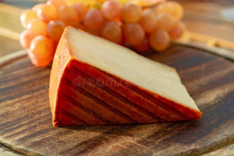 Queso español de la leche de la cabra con la capa de la paprika y las uvas de tabla rosadas maduras foto de archivo