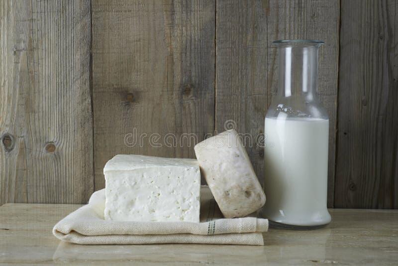 Queso feta fresco con la botella de leche imagenes de archivo