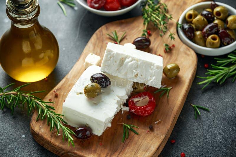 Queso Feta griego del queso con tomillo, romero, aceitunas y paprikas rojos rellenos fotos de archivo libres de regalías