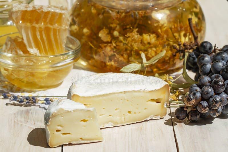 Queso francés suave del camembert con la miel, las uvas negras, la infusión de hierbas y la lavanda Desayuno europeo sano en un b fotos de archivo