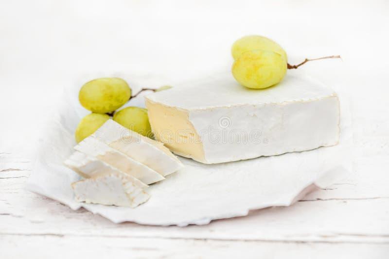 Queso fresco del brie con las rebanadas y uva en rústico blanco en un cortejar imágenes de archivo libres de regalías