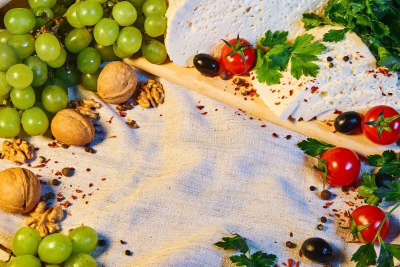 queso georgiano hecho en casa en un tablero de madera, tomates de cereza, nueces, uvas, especias de Imeretian fotos de archivo