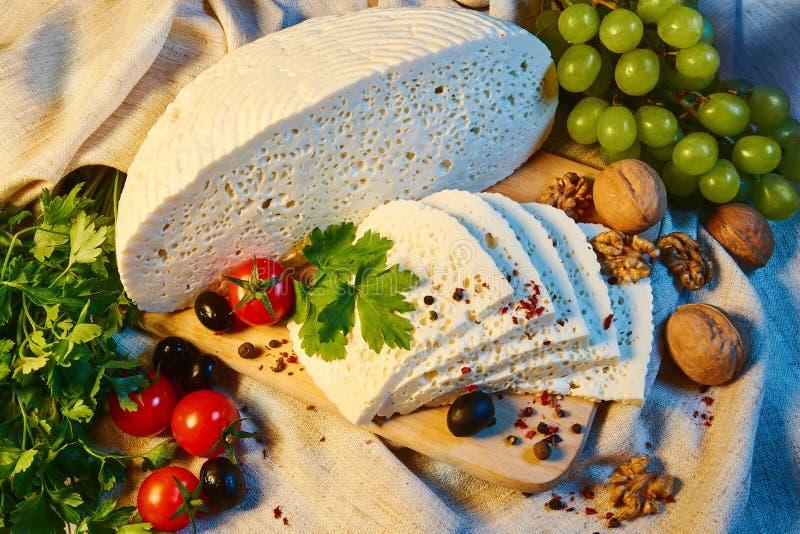 queso georgiano hecho en casa en un tablero de madera, tomates de cereza, nueces, uvas, especias de Imeretian imagenes de archivo