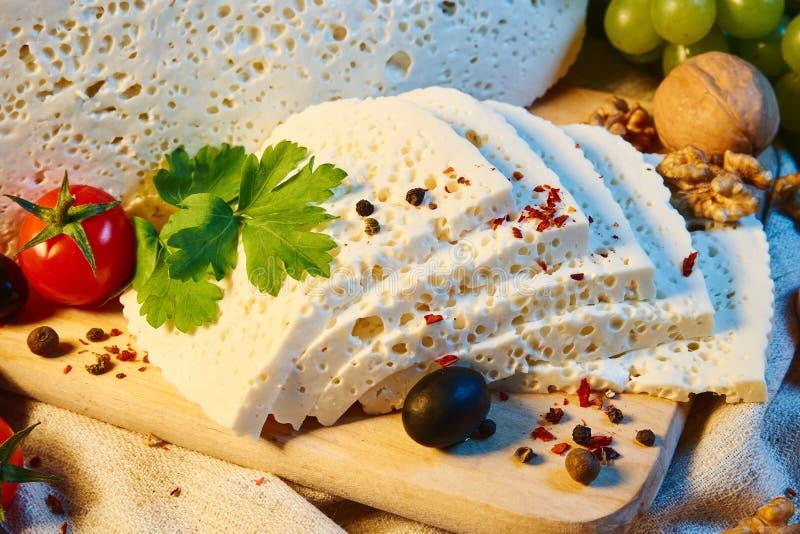 queso georgiano hecho en casa en un tablero de madera, tomates de cereza, nueces, uvas, especias de Imeretian imagen de archivo