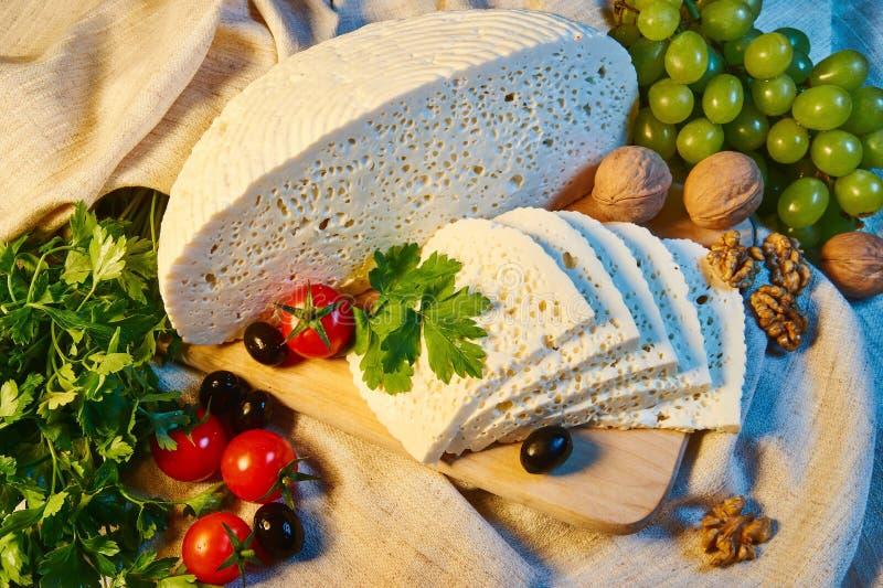 queso georgiano hecho en casa en un tablero de madera, tomates de cereza, nueces, uvas de Imeretian fotografía de archivo libre de regalías