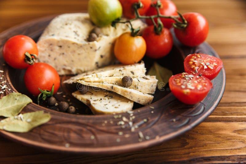Queso hecho en casa, tomate con la especia de la hierba en cerámica Backgr de madera imagen de archivo