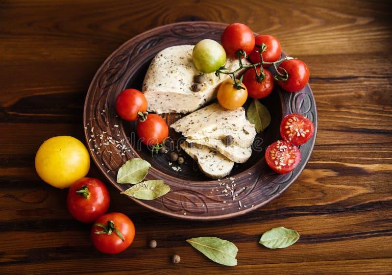 Queso hecho en casa, tomates con la especia de la hierba en cerámica rústica De madera foto de archivo libre de regalías