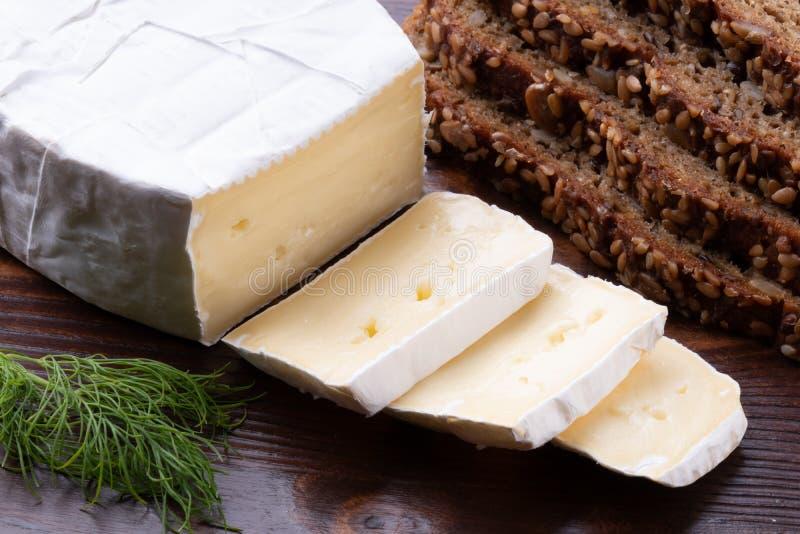 Queso hediondo cortado del camembert con pan en una tabla rústica de madera foto de archivo libre de regalías