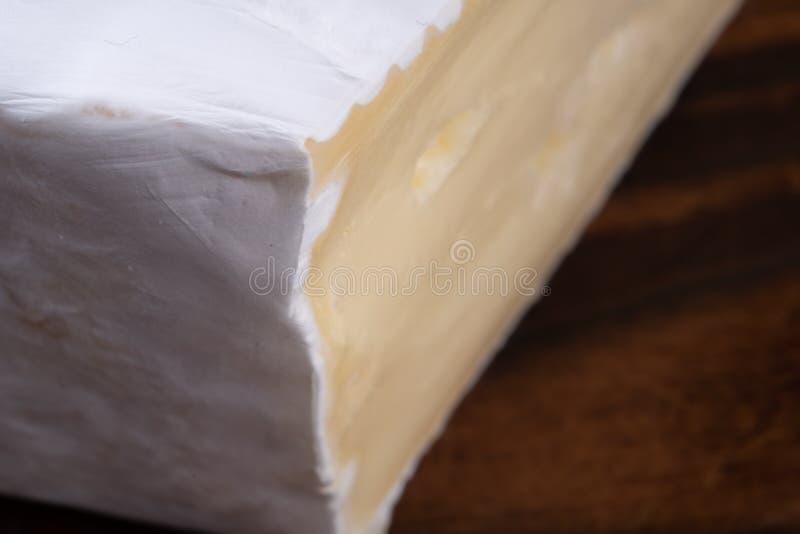 Queso hediondo cortado del camembert en una tabla rústica de madera fotos de archivo