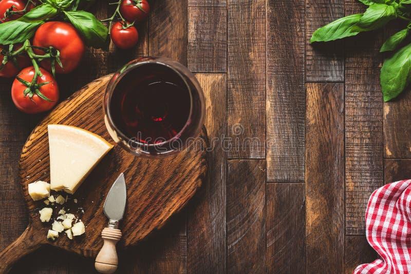 Queso parmesano, tomates, albahaca y vidrio de vino rojo Alimento italiano fotografía de archivo