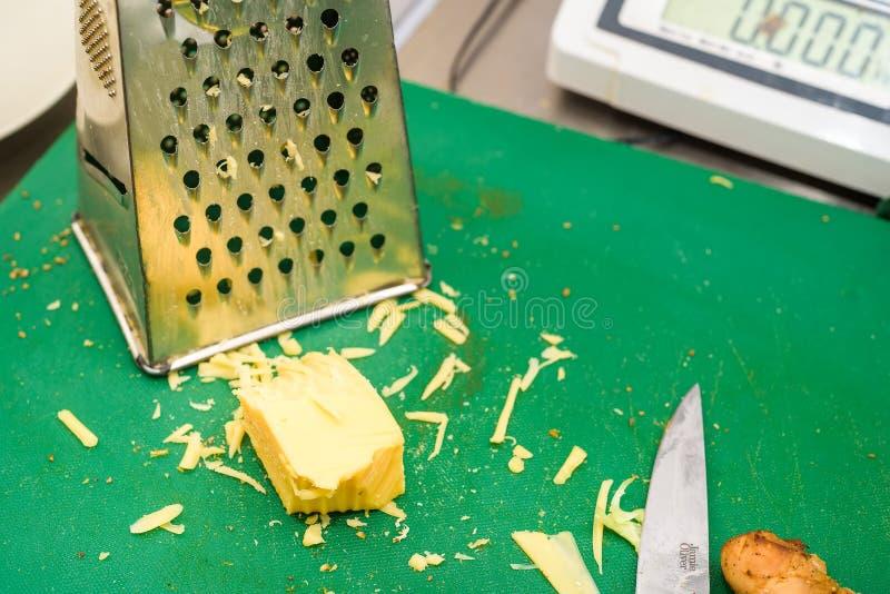 Queso rallado con el rallador y el cuchillo imagen de archivo