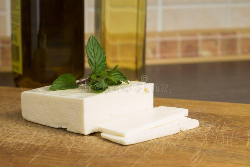 Queso salado cortado en la tabla de cocina foto de archivo libre de regalías