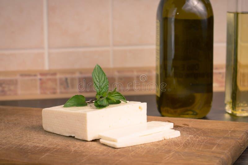 Queso salado cortado en la tabla de cocina imágenes de archivo libres de regalías