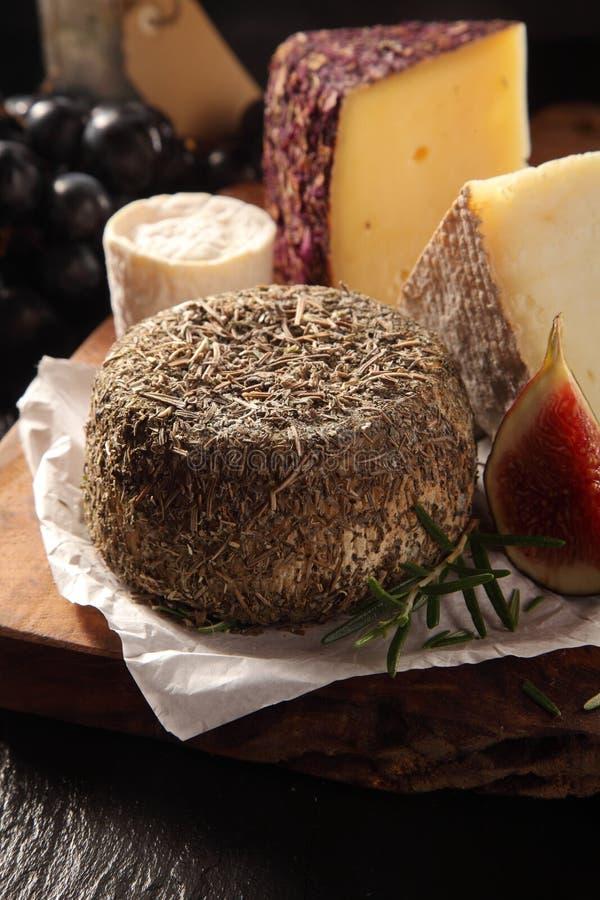 Queso suave cubierto en las hierbas servidas en tablero del queso foto de archivo
