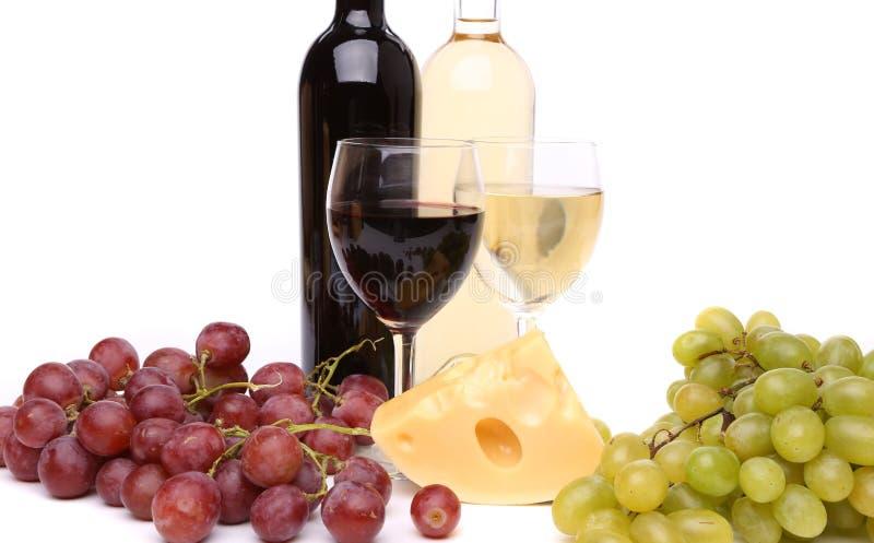 Queso, uva, botellas y vidrios de vino imagenes de archivo