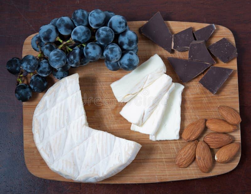 Queso, uvas, chocolate y almendras del brie en un tablero de madera fotos de archivo libres de regalías