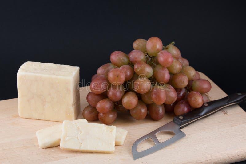 Queso, uvas y un cuchillo del queso fotografía de archivo libre de regalías