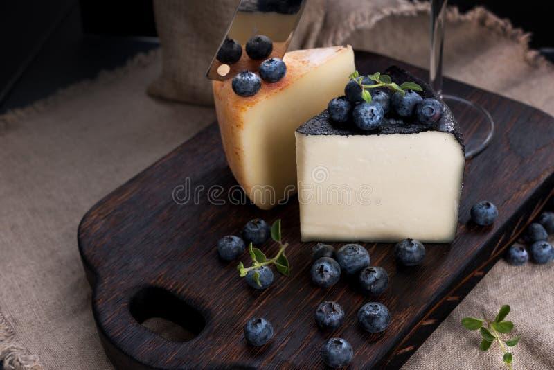 Queso y ar?ndanos blancos del pecorino Cena especial italiana tradicional del queso duro Fondo de madera y foto oscura del estilo fotos de archivo