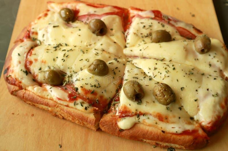 Queso y Olive Pizza Served Mouthwatering en la placa de madera fotos de archivo