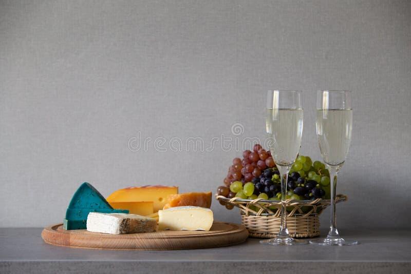 Queso y uvas en cesta de mimbre con el vino blanco foto de archivo libre de regalías
