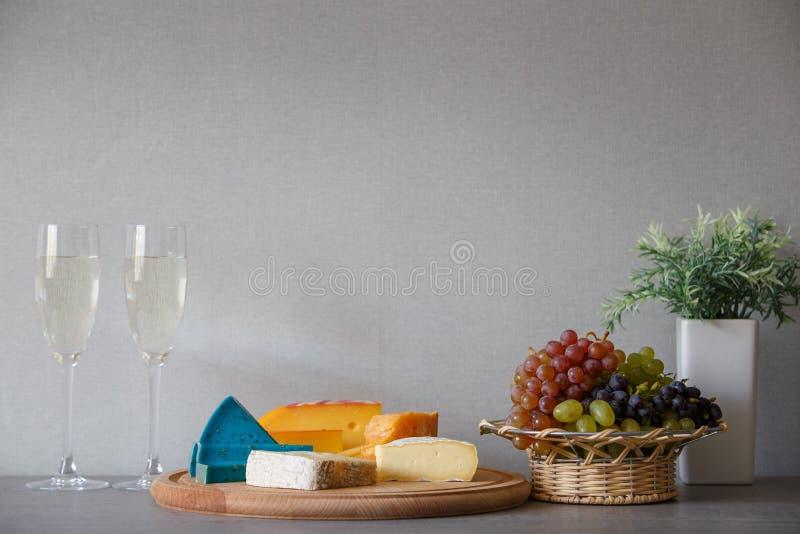 Queso y uvas en cesta de mimbre con el vino blanco imágenes de archivo libres de regalías