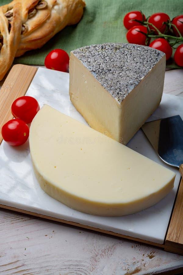 Quesos italianos, queso toscano maduro de las ovejas de Pecorino y queso de la vaca del dolce del provolone servido con pan y tom imagen de archivo libre de regalías